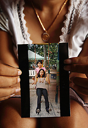 Lisa, 29, holds up a photo of her with her best friend Dede, 25 at top of photograph, who died in 2003 from an unsafe abortion, Jakarta, Indonesia, April 24, 2006. The photo was taken the day before Dede was rushed to hospital with severe bleeding, where she died three days later. It is said by doctors and activists that a woman dies every hour in Indonesia due to unsafe abortions.
