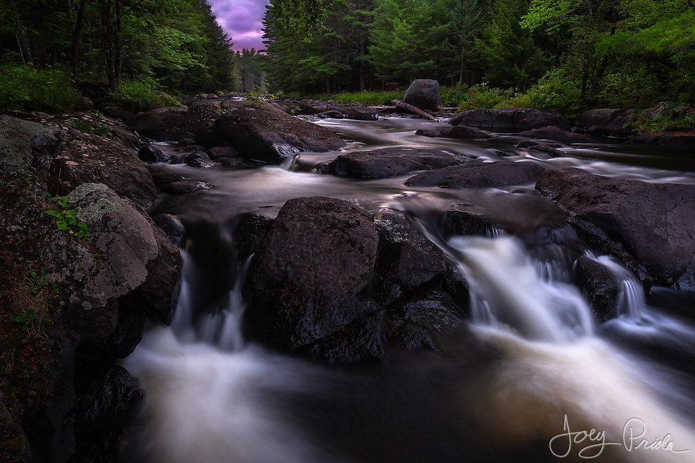 A pristine brook cascades over boulders after a summer sunset in the Adirondacks.