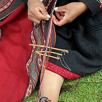 South America, Peru, Chinchero. Woman weaves using foot as loom.