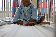 An African toddler with a toy car in a hospital cot on a ward at Clairwood hospital in Durban, South Africa. This hospice is one of the places that BigShoes Foundation provide pediatric palliative care.