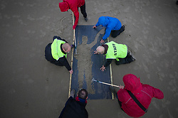 © Licensed to London News Pictures. 11/11/2018. Folkestone, UK. People use a stencil to make an image of a WW1 soldier on the beach at Folkestone, Kent as the weather turns wet and windy during an Armistice Centenary event entitled 'Pages of the Sea'. Portraits are being created by communities on 32 beaches around the UK to say goodbye and thank you, to the millions of men and women who left these shores during the war, many never to return. Lieutenant Wilfred Edward Salter Owen, MC died on 4th November 1918 only days before the Armistice. One of Britain's most celebrated war poets - his short career was directly inspired by the conflict – he composed nearly all his works from August 1917 to September 1918, many published posthumously. Photo credit: Peter Macdiarmid/LNP
