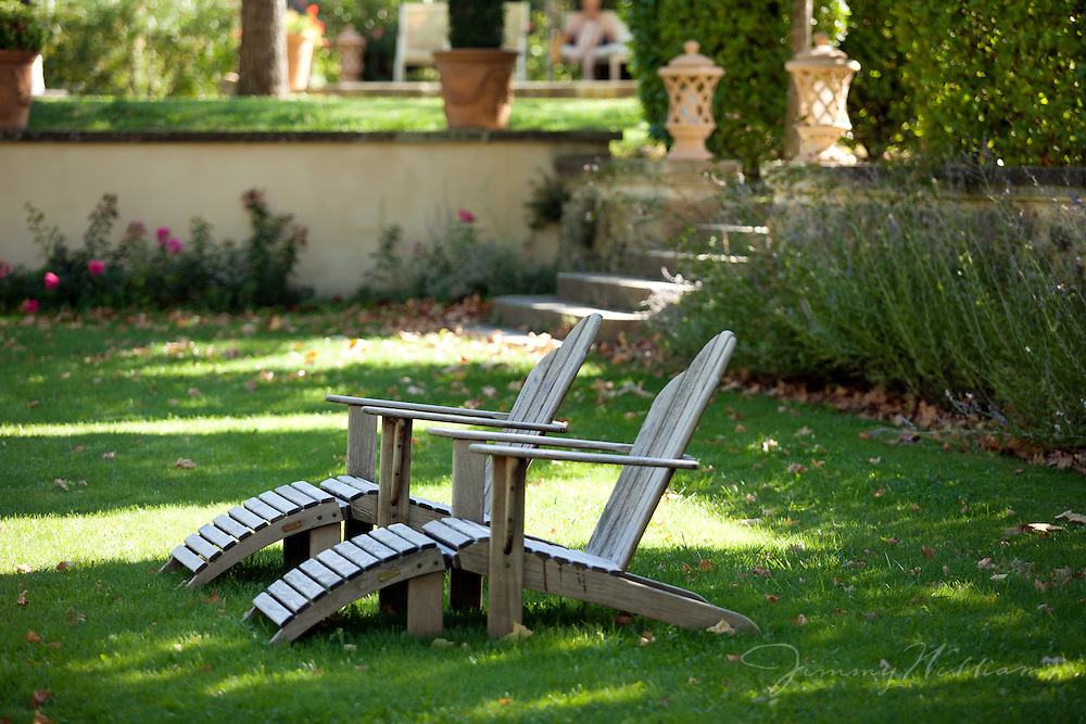 A pair of adirondack chairs wait in the yard for an occupant to relax in