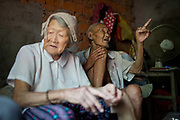 87 year old Dou Shengli and 85 year old He Xiuying sit in their home at a rural village near Fuyang, Anhui Province,  China on 28 August  2013.  As able-bodied adults seek work in cities in hopes of better income, more and more villages in China are inhabited mostly by the elderly and children.
