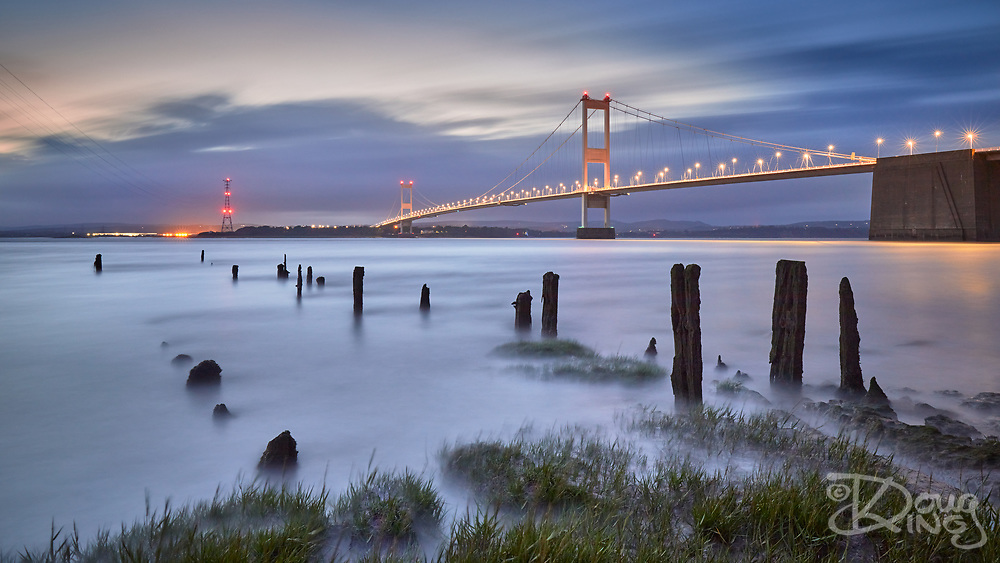 The Severn Bridge at Night with the remnants of a former jetty in the foreground surrounded by a rapidly rising tide.
