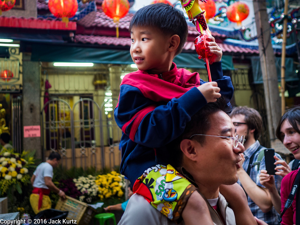 """08 FEBRUARY 2016 - BANGKOK, THAILAND: A boy perched on his father's shoulders watch lion dancers perform for Chinese New Year at a small Chinese shrine in Bangkok's Chinatown district, during the celebration of the Lunar New Year. Chinese New Year is also called Lunar New Year or Tet (in Vietnamese communities). This year is the """"Year of the Monkey."""" Thailand has the largest overseas Chinese population in the world; about 14 percent of Thais are of Chinese ancestry and some Chinese holidays, especially Chinese New Year, are widely celebrated in Thailand.      PHOTO BY JACK KURTZ"""