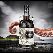 Kraken black spiced rum photographed on a stormy coastline with a tentacle from the mythological Kraken beast reaching in behind the bottle. Photographed by Stuart Freeman.