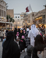 Dusk falls on the popular pedestrian area of Souk Waqif in Doha, Qatar. The flag of Qatar is visible in the background.