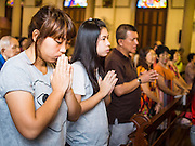 15 FEBRUARY 2015 - BANGKOK, THAILAND: People pray during mass at Santa Cruz Catholic Church in the Kudeejeen neighborhood in Bangkok. Santa Cruz church was established in 1770  and is one of the oldest and most historic Catholic churches in Thailand. The church was originally built by Portuguese soldiers allied with King Taksin the Great. Taksin authorized the church as a thanks to the Portuguese who assisted the Siamese during the war with Burma. Most of the Catholics in the neighborhood trace their family roots to the original Portuguese soldiers who married Siamese (Thai) women. There are about 300,000 Catholics in Thailand in about 430 Catholic parishes and about 660 Catholic priests in Thailand. Thais are tolerant of other religions and although Thailand is officially Buddhist, Catholics are allowed to freely practice and people who convert to Catholicism are not discriminated against.      PHOTO BY JACK KURTZ