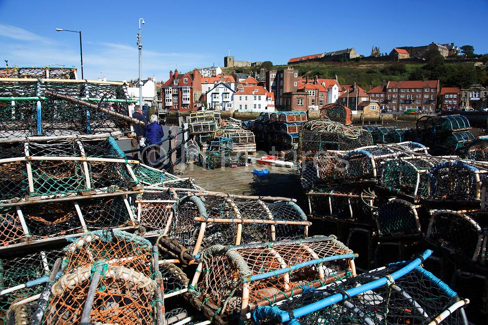 Lobster pots on the quayside at the harbour in Whitby, a seaside town, port in the county of North Yorkshire, originally the North Riding. Situated on the east coast at the mouth of the River Esk. Tourism started in Whitby during the Georgian period and developed. Its attraction as a tourist destination is enhanced by its proximity to the high ground of the North York Moors, its famous abbey, and by its association with the horror novel Dracula. Yorkshire, England, UK.