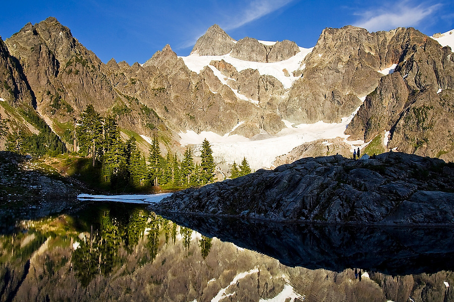 A couple enjoys the views of Mount Shuksan from their camp on the shore of Lake Ann in  Mount Baker-Snoqualmie National Forest, Washington.