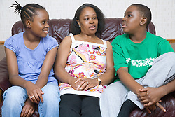 Mother sitting on the sofa with her teenage daughter and son,