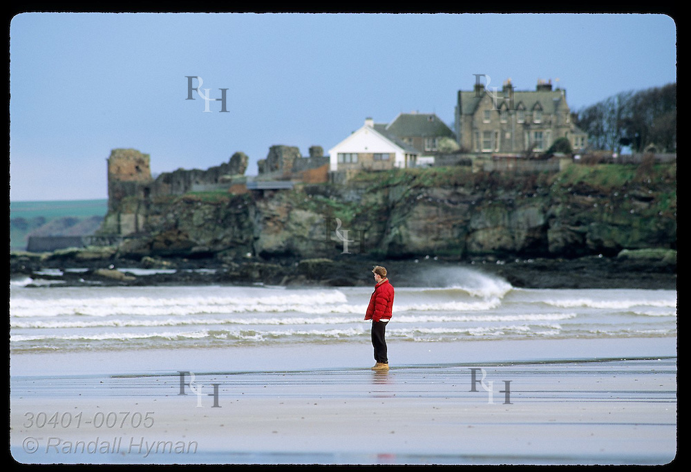 Man surveys sea from beach guarded by ruins of St. Andrews Castle on distant cliffs; St. Andrews. Scotland