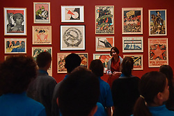 "© Licensed to London News Pictures. 07/11/2017. London, UK.  Students from Thomas Tallis School, Kidbrooke, south London, listen to a talk on Soviet political propaganda posters during their visit to the preview of ""Red Star Over Russia: A Revolution in Visual Culture 1905-55"" at Tate Modern.  The exhibition marks the centenary of the October Revolution and presents the visual history of Russia and the Soviet Union with works drawn from the late graphic designer David King. Photo credit: Stephen Chung/LNP"