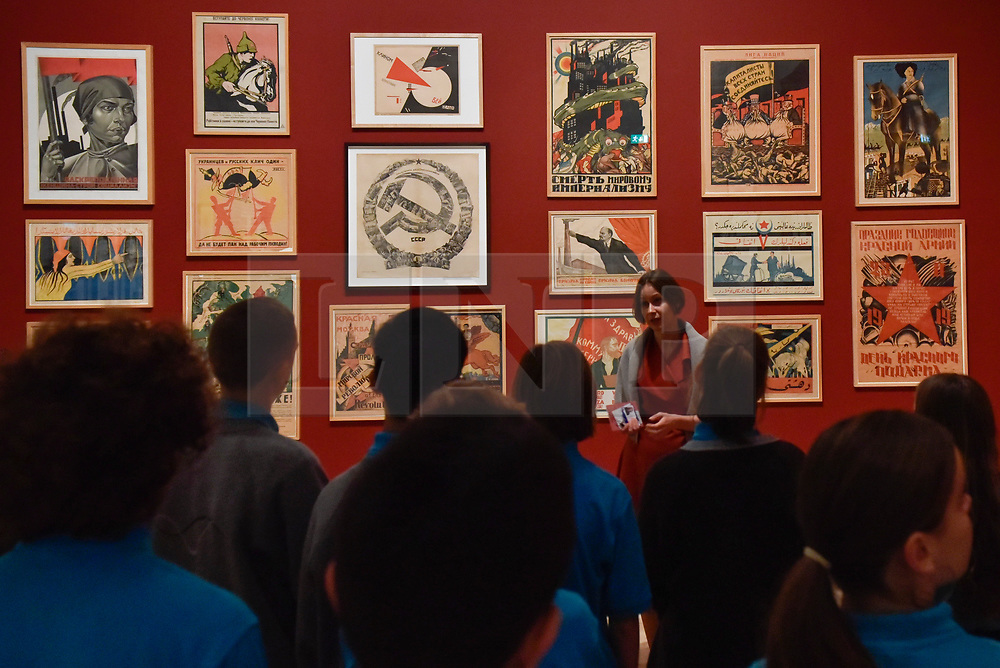 """© Licensed to London News Pictures. 07/11/2017. London, UK.  Students from Thomas Tallis School, Kidbrooke, south London, listen to a talk on Soviet political propaganda posters during their visit to the preview of """"Red Star Over Russia: A Revolution in Visual Culture 1905-55"""" at Tate Modern.  The exhibition marks the centenary of the October Revolution and presents the visual history of Russia and the Soviet Union with works drawn from the late graphic designer David King. Photo credit: Stephen Chung/LNP"""