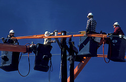 Stock photo of men in cherry pickers working on power lines
