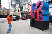 "Couple kissing for a picture with the Love sculpture artwork in the City of London, UK. Robert Indiana's famous ""Love"" sculpture stands at the corner of 99 Bishopsgate – the site of the 1993 IRA bomb 20 years ago."