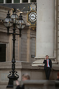 A businessman makes a call below the clock and columns of Cornhill with the Bank of England in the background in the heart of the Square Mile, the capital's historical and financial centre, on 1st November 2017, in the City of London, England.