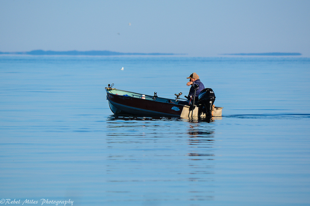 Solitary Fisherman On Lake Michigan On A Calm Peaceful Day