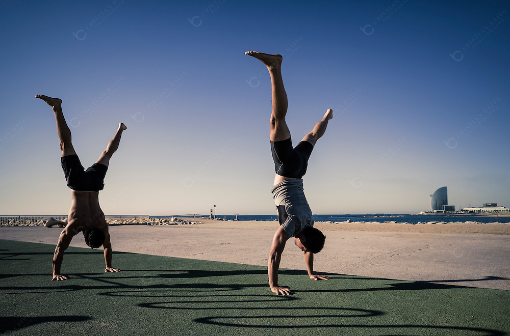 Young men doing headstands as part of their calisthenics workout routine