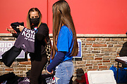 """24 OCTOBER 2020 - DES MOINES, IOWA: A woman picks up a Biden/Harris tee shirt at a Biden """"Get Out the Vote"""" event at La Tapatia in Des Moines. Democrats and Republicans held rival Get Out the Vote (GOTV) events in Des Moines Saturday. Democrats and the Biden/Harris campaign held a voter registration and early balloting events at a Mexican grocery store to mobilize the Latino community and then marched to the Polk County Auditor's Office to support early voting efforts. Supporters of President Trump participated in a motorcade that drove through Des Moines flying Trump 2020 flags and honking their car and truck horns.      PHOTO BY JACK KURTZ"""