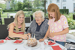 Family celebrating birthday of grandmother in rest home yard, Bavaria, Germany