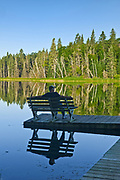 tourist sitting on bench admiring the view of a northern lake in the morning<br />