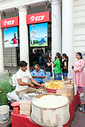 A chaat wallah (snack food vendor) makes a dish for waiting customers on the pavement in Connaught Place, New Delhi.