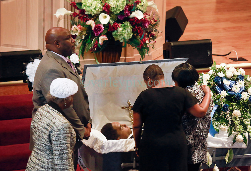 03 June 2014. New Orleans, Lousiana. <br /> Mother and grandmother take a last look at teenage shooting victim Dwayne Matthew Joseph at the Franklin Avenue Baptist Church. 17 year old Joseph was shot and killed following an altercation in the street May 26th. Raised by his great grandmother Catherine Robinson, family and friends confirmed Dwayne was a good kid who went to church, looked after his younger siblings and had never been in trouble with the law. Dwayne's older brother Damien preceded him in death. He too was shot dead in February 2011 aged just 19 years.<br /> Photo; Charlie Varley/varleypix.com