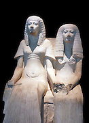 Limestone statue of a husband and wife. Egyptian18th or 19th Dynasty, around 1300 BC. Unidentified couple. The man wears a long detailed wig, and a long robe with long wide slee