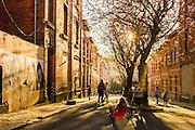 Kinderen spelen in de rue des Artisans in de wijk Elsene van Brussel. In deze straat is elk huis dichtgetimmerd of gemetseld. Bomen staan hier in het midden van de straat en ruimte om te spelen is er genoeg in zo'n verlaten straat.