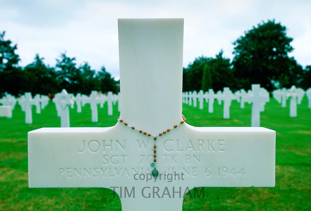 Headstones at a United States Military Cemetery at Utah Beach in Normandy, France.  Flowers have been left beside one of the crosses.