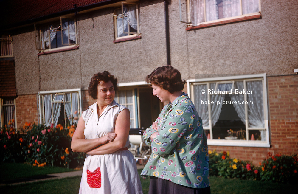 Two mothers and neighbours gossip with arms folded outside their houses on an Essex estate in the early nineteen sixties.