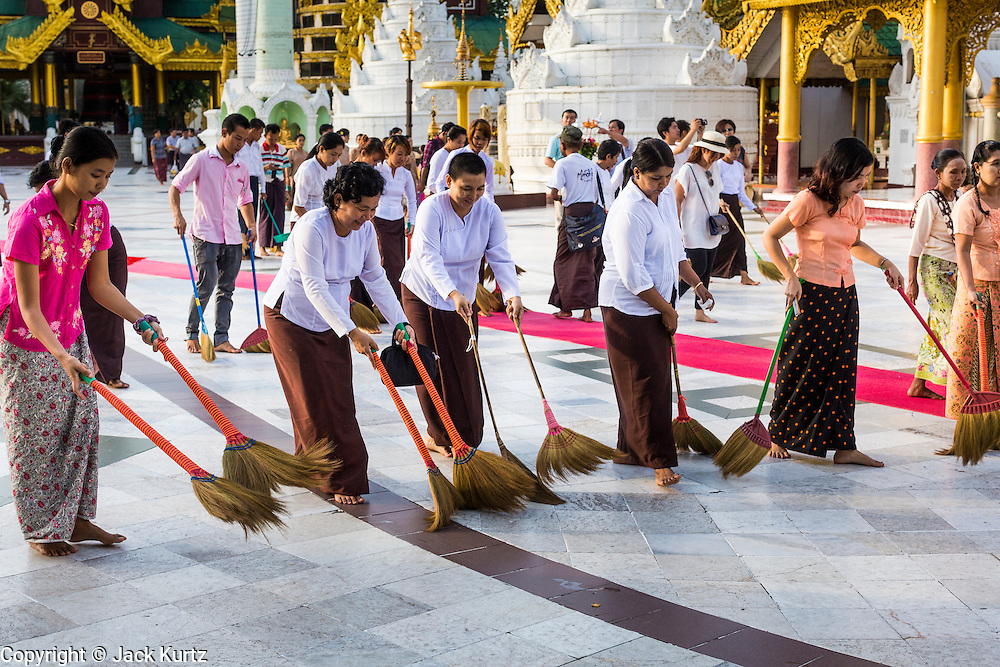 """15 JUNE 2013 - YANGON, MYANMAR:  Women who volunteer to """"make merit"""" clean the grounds of Shwedagon Pagoda. Shwedagon Pagoda is officially known as Shwedagon Zedi Daw and is also called the Great Dagon Pagoda or the Golden Pagoda. It is a 99 meter (325 ft) tall pagoda and stupa located in Yangon, Burma. The pagoda lies to the west of on Singuttara Hill, and dominates the skyline of the city. It is the most sacred Buddhist pagoda in Myanmar and contains relics of the past four Buddhas enshrined: the staff of Kakusandha, the water filter of Koṇāgamana, a piece of the robe of Kassapa and eight strands of hair from Gautama, the historical Buddha. Burmese believe the pagoda was established as early ca 540BC, but archaeological suggests it was built between the 6th and 10th centuries. The pagoda has been renovated numerous times through the centuries. Millions of Burmese and tens of thousands of tourists visit the pagoda every year, which is the most visited site in Yangon. PHOTO BY JACK KURTZ"""