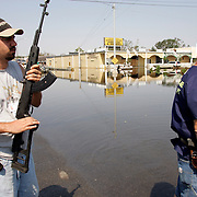 NEW ORLEANS, LA - September 4, 2005:  Heavily armed private security personnel guard firefighters searching flooded New Orleans, LA on Sept. 4, 2005 for survivors of Hurricane Katrina. Security was needed to ward off rioters and criminals. (Photo by Todd Bigelow/Aurora)