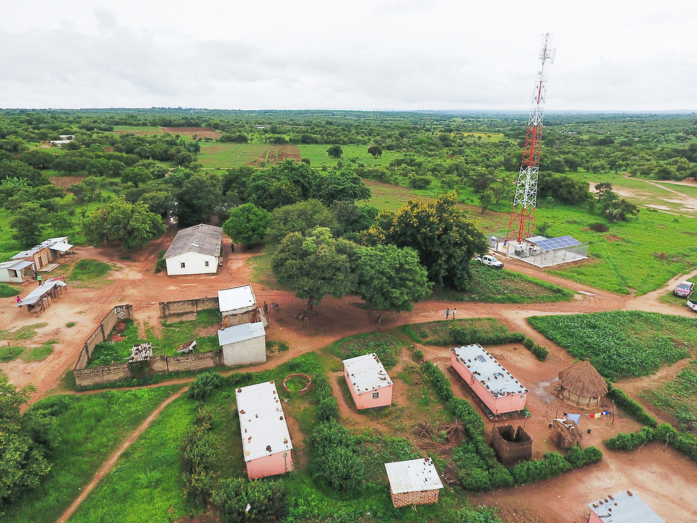 INDIVIDUAL(S) PHOTOGRAPHED: N/A. LOCATION: IHS Telecommunications Tower, Nkondora Village, Near Chongwe, Lusaka Province, Zambia. CAPTION: Aerial photo of the buildings surrounding the IHS Tower, with the tower in the background.