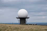 Radar station on top of Titterstone Clee Hill on 22nd July 2020 in Cleedownton, United Kingdom. Titterstone Clee Hill, sometimes referred to as Titterstone Clee or, incorrectly, Clee Hill, is a prominent hill in the rural English county of Shropshire, rising at the summit to 533 metres above sea level. It is one of the Clee Hills, in the Shropshire Hills Area of Outstanding Natural Beauty. Most of the summit of the hill is affected by man-made activity, the result of hill fort construction during the Bronze and Iron Ages and, more recently, by years of mining for coal and quarrying for dolerite, known locally as dhustone, for use in road-building. Many derelict quarry buildings scattered over the hill are of industrial archaeological interest as very early examples of the use of reinforced concrete. Several radar domes and towers operate on the summit of the hill. The largest of the radar arrays is part of the National Air Traffic Services NATS radar network, and covers one of 30 overlapping regions of UK airspace. The one on Titterstone Clee monitors all aircraft within a 100-mile radius.