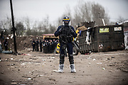 March 1, 2016 - Calais, France -<br /> <br /> Destruction Of Calais Jungle Camp Continues<br /> <br /> Police officer look stand guard as the 'jungle' migrant camp is cleared on March 01, 2016 in Calais, France. Authorities return to clear migrant shelters from more parts of the 'Jungle' migrant camp in Calais and try to move people to shipping containers on another part of the site. French demolition teams began dismantling huts yesterday. Resistance is expected to continue and overnight riot police fired teargas at migrants who were throwing stones. A court ruling on Thursday approved a French Govt plan to clear part of the site. Authorities say approx 1,000 migrants are to be affected out of 3,700 people - many of them refugees from Syria and Iraq - who are thought to live in the camp. Mayor of Calais Natacha Bouchart has demanded the closure of the site for several weeks following several recent clashes with police  <br /> ©Exclusivepix Media