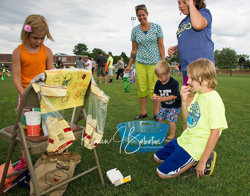 Jameson Halligan keeps his eyes closed tight as he plays the Duck Pick game run by Makenna MacDonald and Aaron St Gelais at the Opechee Peanut Carnival on Thursday evening.  (Karen Bobotas/for the Laconia Daily Sun)