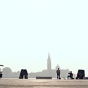 Men fishing with a view to St Mark's Campanile, Venice, Italy