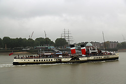 © Licensed to London News Pictures. 11/10/2013. Passengers hid from the rain as the he famous and much loved paddle steamer Waverley passed maritime Greenwich today as she nears the end of her season on the Thames. Waverley seen here passing the Cutty Sark. Credit : Rob Powell/LNP