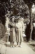 female posing with grandmother with grandfather in the background 1939