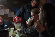Brooke Hubbard-Sizen pours raw milk for her classmates and fellow Green Acres employees Valerie Thorburn, middle, and Brooke Parent, right, as they sit down for their weekly dinner and meeting with Craig and Joan Wortman in Bethel, Vt. Monday, April 18, 2016. Every Monday the Wortmans host their employees to assign milking and chore shifts and discuss breeding schedules and any health issues in the herd. (Valley News - James M. Patterson) Copyright Valley News. May not be reprinted or used online without permission. Send requests to permission@vnews.com.