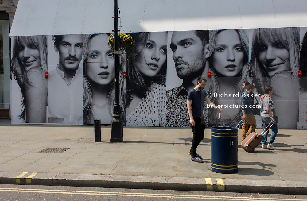 A Londoner drops a Coke can into a rubbish bin beneath the panels of a large poster for the H&M clothing brand on Regent Street, London.
