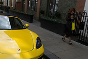 A young woman carrying a yellow handbag and looking at her phone, walks past a matching yellow Porsche sports car in London's Soho, the West End, on 2nd July 2020, in London, England.