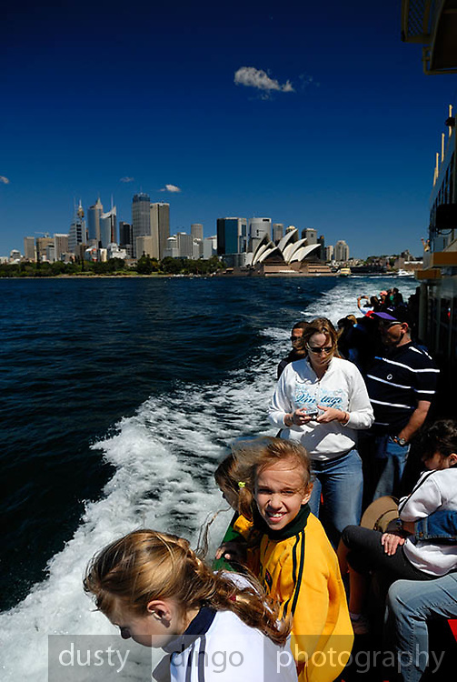 Passengers on deck of Sydney Ferry, Sydney Opera House and Circular Quay skyline in background. Sydney, Australia