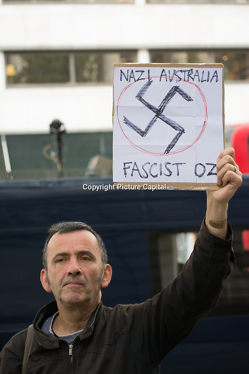 A man holding a banner written Nazi Australia, Facist Oz conspiracy theorist Australia tyranny Government disguised as Public Health is a test for New World Order outside Australia House, London, UK. October 1st 2021.