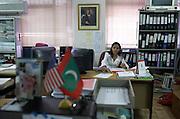 Female employee of Cyprea Marine Foods works beneath portrait of Maldives president Gayoom in capital Male.
