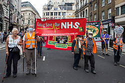 Campaigners from Ealing Save Our NHS join thousands of people attending a United Against The Tories national demonstration organised by the People's Assembly Against Austerity in protest against the policies of Prime Minister Boris Johnson's Conservative government on 26th June 2021 in London, United Kingdom. The demonstration contained blocs from organisations and groups including Palestine Solidarity Campaign, Stand Up To Racism, Stop The War Coalition, Extinction Rebellion, Kill The Bill and Black Lives Matter as well as from trade unions Unite and the CWU.