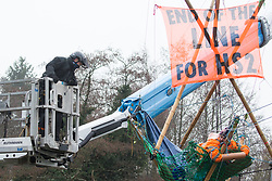Denham, UK. 8th December, 2020. Bailiffs use a large cherry picker to approach Dan Hooper, widely known as Swampy during the 1990s, who is sitting on a bamboo tripod positioned in the river Colne. The climate and roads activist had occupied the tripod the previous day in order to delay the building of a bridge as part of works for the controversial HS2 high-speed rail link and a large security operation involving officers from at least three police forces, the National Eviction Team and HS2 security guards was put in place to facilitate his removal.