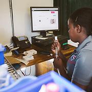 INDIVIDUAL(S) PHOTOGRAPHED: Unknown. LOCATION: Sacré-Cœur Hospital, Milot Commune, Cap-Haïtien, Haïti. CAPTION: A nurse aide fills a syringe with medication in the maternity ward at Sacré-Cœur Hospital in Milot.